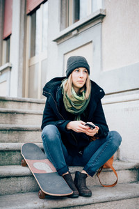 young beautiful hipster sporty blonde woman in town with skate using smartphone
