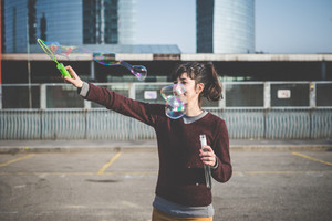 young beautiful hipster woman bubble blower in the city