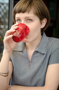 young beautiful hipster woman drinking at the bar