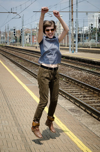 young beautiful hipster woman jumping in the station