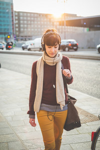young beautiful hipster woman listening music with headphones in the city