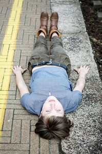 young beautiful hipster woman lying on the ground in the city