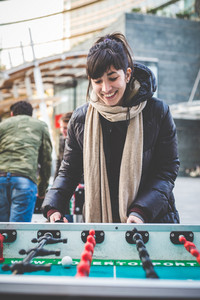 young beautiful hipster woman playing table football in the city