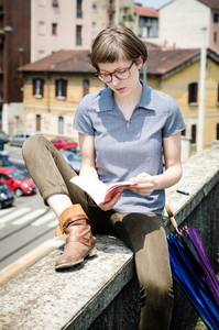 young beautiful hipster woman reading book in the city