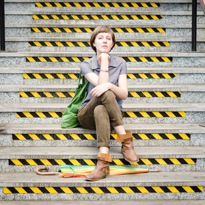 young beautiful hipster woman sitting on the stairs in the city