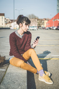 young beautiful hipster woman using smart phone in the city