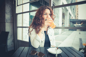 young beautiful hipster woman with red curly hair at the bar