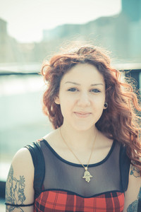 young beautiful hipster woman with red curly hair in the city