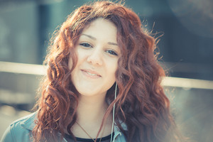 young beautiful hipster woman with red curly hair listening music in the city
