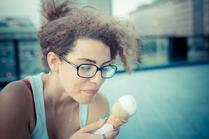 young beautiful long curly hair hipster woman eating ice cream in the city
