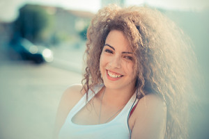 young beautiful long curly hair hipster woman in the city