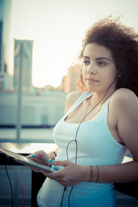 young beautiful long curly hair hipster woman listening to music with tablet in the city