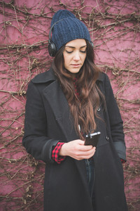young beautiful long hair model woman living the city in winter outdoor city listening to music with headphones