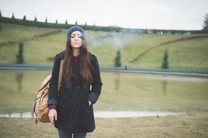 young beautiful long hair model woman living the city in winter outdoor city smoking cigarette