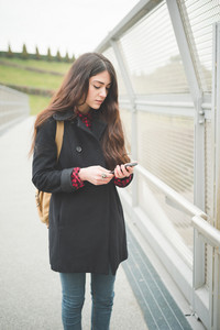 young beautiful long hair model woman living the city in winter outdoor city using smartphone