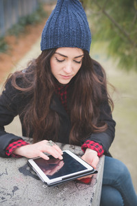 young beautiful long hair model woman living the city in winter outdoor city using tablet connected wireless online