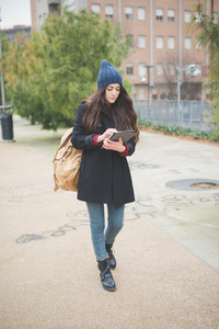 young beautiful long hair model woman living the city in winter outdoor city using tablet walking connected wireless online