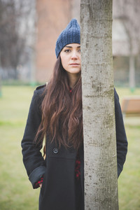 young beautiful long hair model woman melancholic and pensive hiding under a tree in a city park in winter - concept of humans feelings