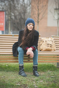 young beautiful long hair model woman melancholic and pensive sitting on a bench in a city park in winter looking downward - relaxing, human feelings concept