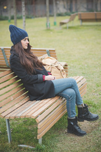 young beautiful long hair model woman melancholic and pensive sitting on a bench in a city park in winter - relaxing, humans feelings concept