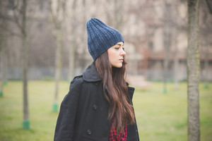 young beautiful long hair model woman pensive and seriouswalking in the city park in winter  - concept of humans emotion