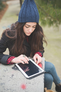 young beautiful long hair model woman pensive sitting on a bench using a tablet - technology, social network, relax concept