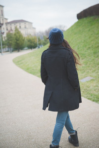 young beautiful long hair model woman walking in the city outdoor in winter from back - concept of human emotion