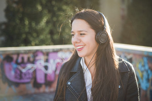 young beautiful long hair woman in town during sunset backlight listening music with headphones