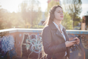 young beautiful long hair woman in town during sunset backlight listening to music with headphones