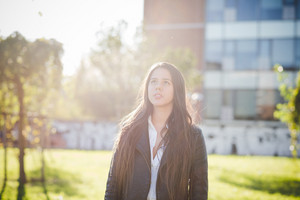 young beautiful long hair woman in town during sunset backlight