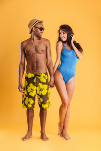 Young beautiful loving couple in beachwear holding hands and looking at each other isolated on the orange background