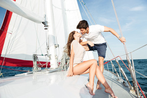 Young beautiful married couple kissing on the yacht on vacation