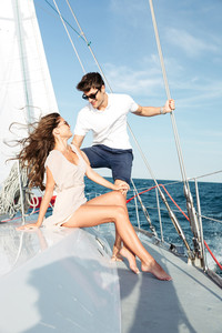 Young beautiful married couple relaxing together on the yacht
