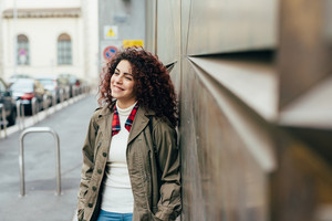 Young beautiful mixed race woman outdoor in the city leaning on a wall overlooking smiling - happiness, having fun, carefree concept