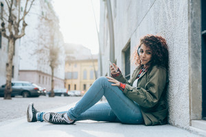 Young beautiful mixed race woman sitting on the ground listening music with headphones and smart phone hand hold - technology, music, happiness concept