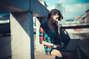 young beautiful model woman using notebook in the city