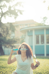 young beautiful moroccan curly woman blowing bubbles at the park