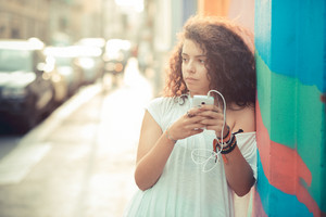 young beautiful moroccan curly woman using smartphone in the city