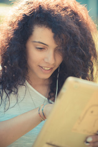 young beautiful moroccan curly woman using tablet at the park