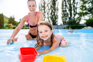 Young beautiful mother in bikini playing with her daughter in swimming pool in aqua park. Summer heat and water.
