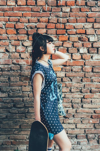 Young beautiful nonconformist asiatic woman posing outdoor in the city on a brick wall overlooking - eccentric, stylish, hairstyle concept