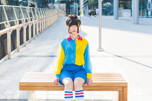 Young beautiful nonconformist asiatic woman sitting on a wooden bench outdoor in the city, looking at camera, pensive - thoughtful, serious, eccentric concept