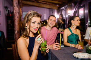 Young beautiful people with cocktails in bar or club having fun