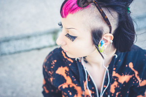 young beautiful punk dark girl listening music in urban landscape