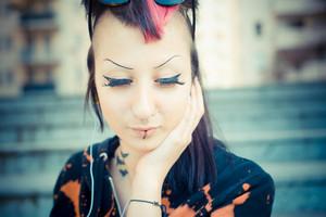young beautiful punk dark girl listening music in urban landscape