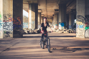 young beautiful punk dark girl riding bike in urban landscape