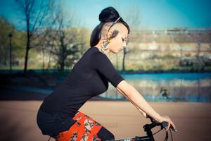 young beautiful punk dark girl riding bike in urban landscape