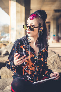 young beautiful punk dark girl usign tablet in urban landscape