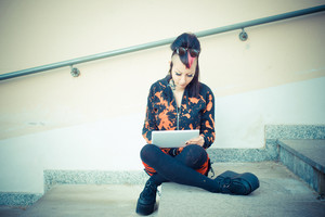 young beautiful punk dark girl using tablet in urban landscape