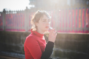 young beautiful red dressed vintage hipster woman at the station smoking cigarette